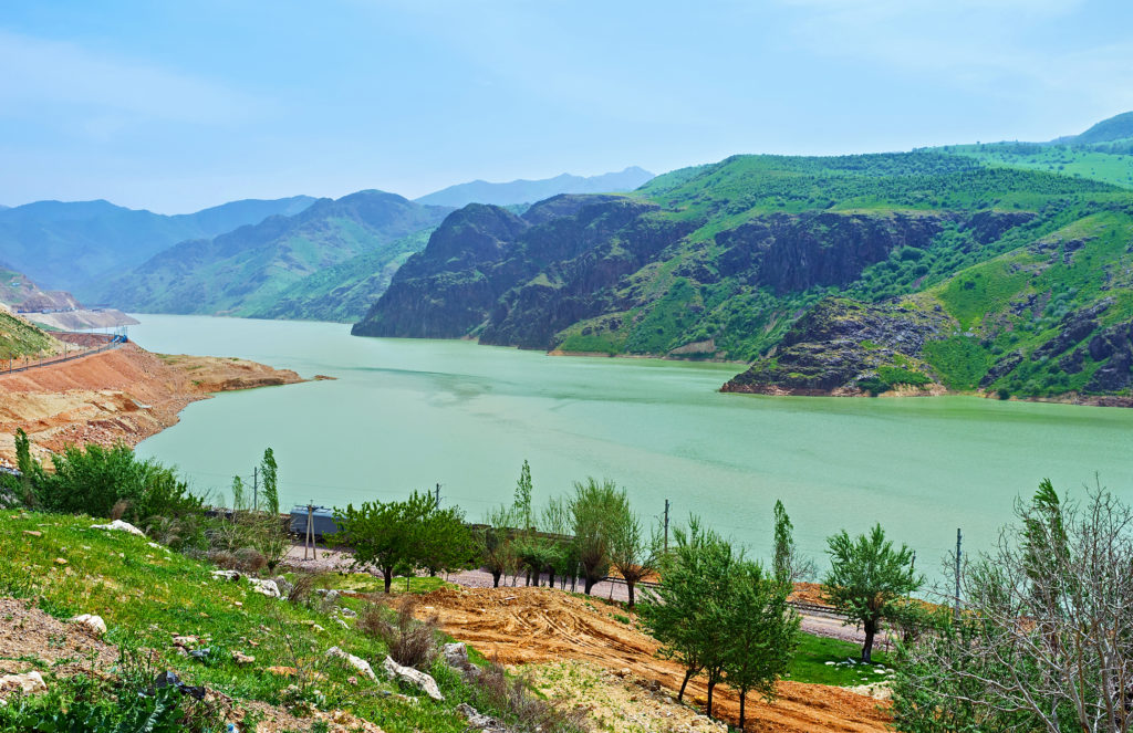 The green waters of the Achangaran reservoir with the Qurama Mountains on the background, Uzbekistan.